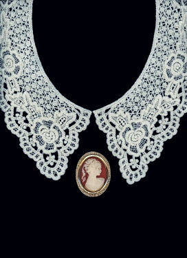 Magdalena Russocka white lace collar and cameo brooch on black background