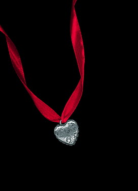 Magdalena Russocka silver heart shaped locket with red ribbon on black background