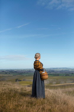 Mary Wethey WOMAN WITH SHAWL AND BASKET IN RURAL LANDSCAPE