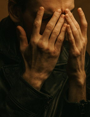 Maria Yakimova MAN IN LEATHER JACKET COVERING FACE WITH HANDS