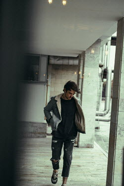 Maria Yakimova MAN WITH RIPPED JEANS WALKING OUTSIDE MODERN BUILDING