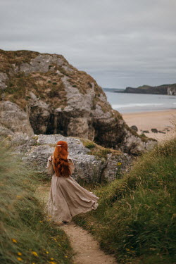 Rebecca Stice WOMAN WITH RED HAIR WALKING ON PATH TO BEACH