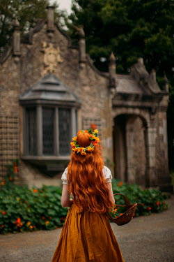 Rebecca Stice GIRL WITH RED HAIR GARLAND AND BASKET OUTSIDE BUILDING