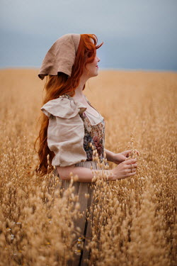 Rebecca Stice GIRL WITH RED HAIR STANDING IN GOLDEN FIELD