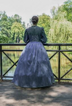 Jaroslaw Blaminsky HISTORICAL WOMAN ON BRIDGE BY RIVER WITH TREES