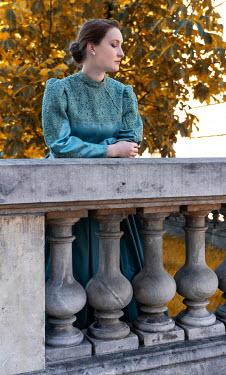 Jaroslaw Blaminsky HISTORICAL WOMAN LEANING ON GRAND STONE WALL