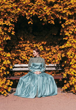 Jaroslaw Blaminsky HISTORICAL WOMAN SITTING ON BENCH WITH AUTUMN LEAVES