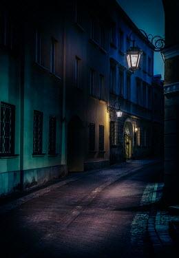 Jaroslaw Blaminsky EMPTY COBBLED STREET WITH BUILDINGS AT NIGHT