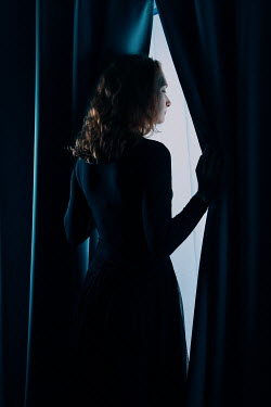Magdalena Russocka woman peeking out from behind the curtains