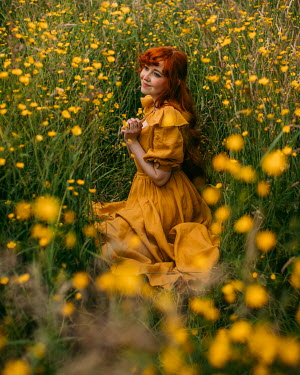 Rebecca Stice WOMAN WITH RED HAIR SITTING WITH YELLOW FLOWERS