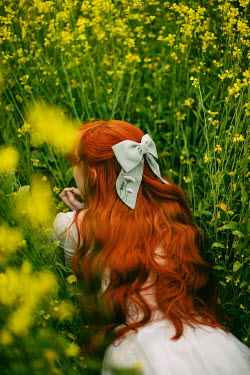 Rebecca Stice WOMAN WITH RED HAIR LYING IN YELLOW FLOWERS