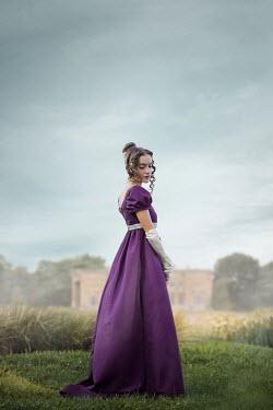 Ildiko Neer Regency woman standing in garden by mansion