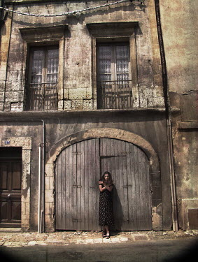 Gary Isaacs WOMAN STANDING OUTSIDE WEATHERED BUILDING
