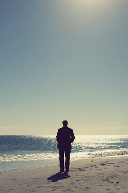 Susan Fox SILHOUETTED MAN ON BEACH WITH SHIMMERING SEA