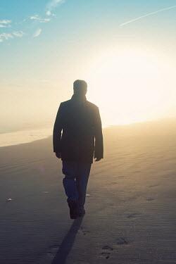 Susan Fox SILHOUETTED MAN WALKING ON SUNLIT BEACH