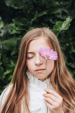 Isabelle Lafrance YOUNG GIRL COVERING EYE WITH FLOWER OUTDOORS