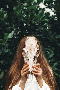 Isabelle Lafrance YOUNG GIRL COVERING FACE WITH ANIMAL SKULL OUTDOORS