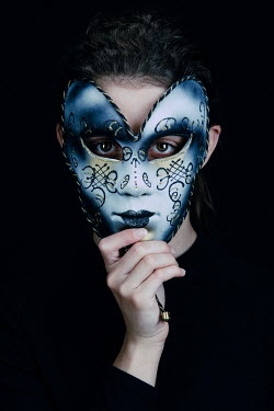 Magdalena Russocka young woman covering her face with venetian mask