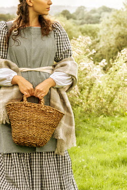 Stephen Mulcahey HISTORICAL WOMAN CARRYING BASKET IN COUNTRYSIDE