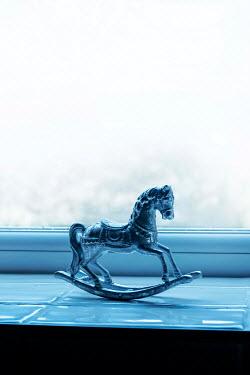 Stephen Mulcahey SILVER ROCKING HORSE ON WINDOW SILL