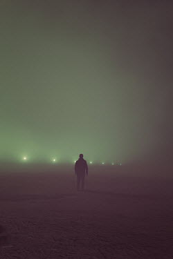 Andrei Cosma SILHOUETTED MAN STANDING IN FOGGY FIELD WITH LIGHTS