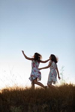 Kerstin Marinov TWO GIRLS RUNNING IN SUMMERY COUNTRYSIDE
