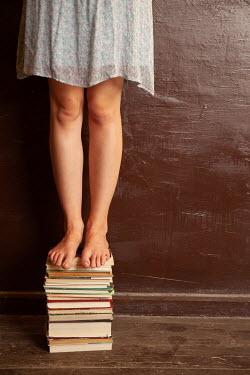 Kerstin Marinov BAREFOOT GIRL STANDING ON PILE OF BOOKS