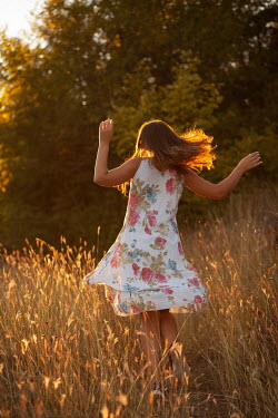 Kerstin Marinov GIRL IN FLORAL DRESS DANCING IN COUNTRYSIDE