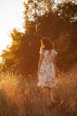 Kerstin Marinov WOMAN IN FLORAL DRESS WALKING IN SUNLIT COUNTRYSIDE