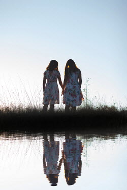 Kerstin Marinov TWO GIRLS HOLDING HANDS REFLECTED IN RIVER