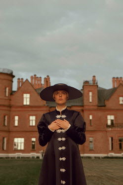 Natasha Yankelevich WOMAN IN BLACK ROBE AND HAT OUTSIDE MANSION