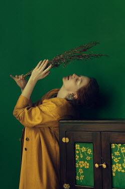 Natasha Yankelevich WOMAN. HOLDING DRIED PLANT INDOORS