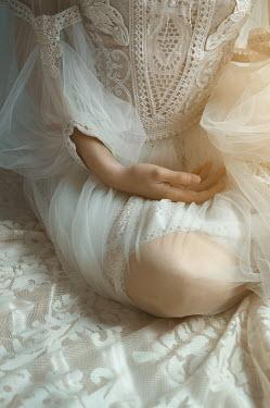 Natasha Yankelevich WOMAN IN WHITE LACE AND CHIFFON SITTING ON BED