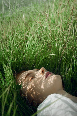 Natasha Yankelevich WOMAN WITH RED HAIR LYING IN GRASS