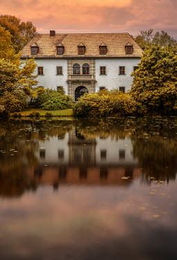 Jaroslaw Blaminsky LARGE HOUSE REFLECTED IN LAKE AT SUNSET