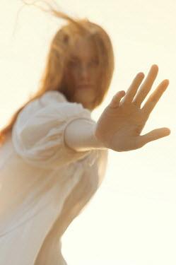 Natasha Yankelevich WOMAN WITH RED HAIR RAISING HAND OUTDOORS