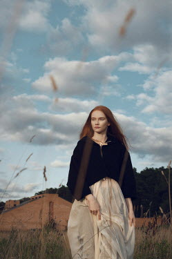 Natasha Yankelevich WOMAN WALKING WITH BUILDING IN COUNTRYSIDE