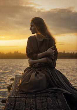 Natasha Yankelevich YOUNG GIRL SITTING ON JETTY AT SUNSET