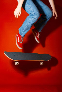 Robin Macmillan TEENAGER IN JEANS JUMPING WITH SKATEBOARD
