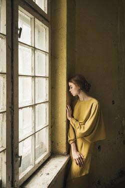 Dorota Gorecka DAYDREAMING GIRL INDOORS BY SHABBY WINDOW
