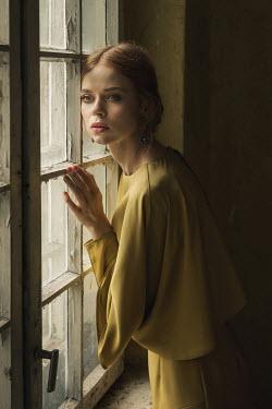 Dorota Gorecka SERIOUS GIRL INDOORS WATCHING AT SHABBY WINDOW