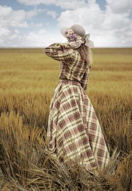 Jaroslaw Blaminsky WOMAN WITH TARTAN DRESS AND HAT STANDING IN FIELD