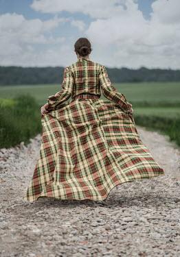 Jaroslaw Blaminsky WOMAN IN TARTAN GOWN WALKING IN COUNTRYSIDE