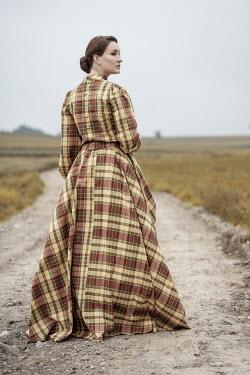 Jaroslaw Blaminsky WOMAN IN TARTAN GOWN STANDING ON COUNTRY ROAD