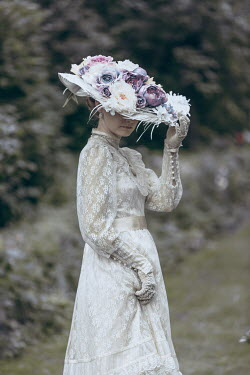 Magdalena Russocka historical woman wearing hat standing in garden