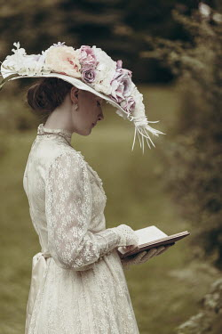 Magdalena Russocka historical woman wearing hat reading book in garden