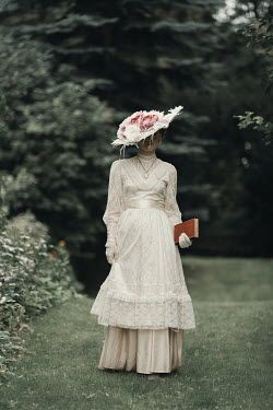 Magdalena Russocka historical woman wearing hat holding book walking in garden