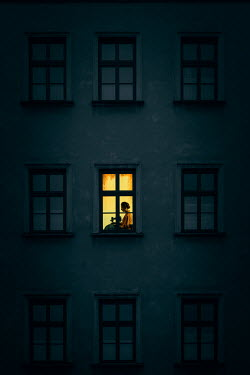 Magdalena Russocka woman working at vintage sewing machine in window of old townhouse at night
