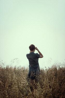Magdalena Russocka teenage girl standing in field shielding her eyes from sun
