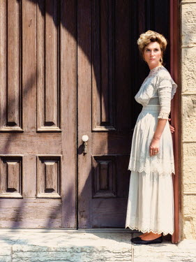 Elisabeth Ansley BLONDE HISTORICAL WOMAN STANDING OUTSIDE BY DOORWAY